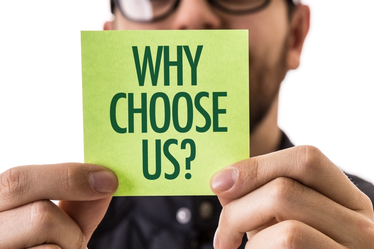 someone holding a sticky note that says why choose us?