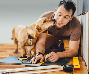 Man doing construction with dog licking his face